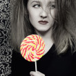 Stock Photo: Young woman with a sugar candy