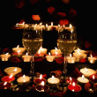 Stock Photo: Wine glasses, candles and petals