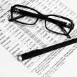 Glasses, financial documents and pencil - Stock Photo