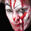 Green-eyed mime with blood on face - Stock Photo