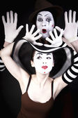 Two mimes in hats on black background — Stock Photo