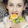 Young woman biting sugar candy — Stock Photo #1950924