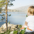 Child seated on the shores of  Inlet. - Stock Photo