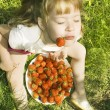 Girl eating strawberries. - Stock Photo