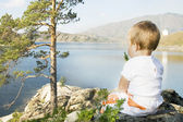Child seated on the shores of Inlet. — Stock Photo