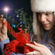 Young Woman Unwrapping Christmas Gift — Stock Photo