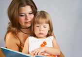 Two sisters read the book — Stock Photo