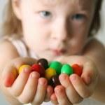 klein meisje de handen de snoepjes — Stockfoto