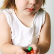 Small girl chews the candies — Stock Photo #1624224