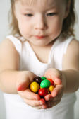 Small girl the hands the candies — Stock Photo