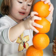 Girl and 4 oranges — Stock Photo