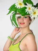 Beauty girl with flowers in her hat — Stock Photo