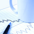 Pen and cup on stock chart — Stockfoto #1592744