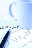 Pen and cup on stock chart — Stockfoto