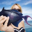 The woman holds in hand blue sea fish — Stock Photo #1786940