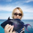 The woman holds in hand blue sea fish — Stock Photo #1786955