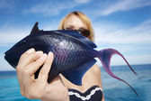 The woman holds in hand blue sea fish — Stock Photo