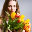 Stock Photo: Beautiful woman holding tulips