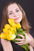 Beautiful woman holding tulips — Stock Photo