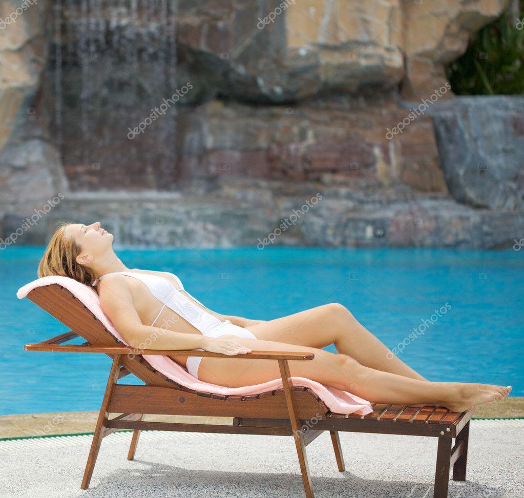 Азиатская девушка шалит в бассейне и на шезлонге  389111
