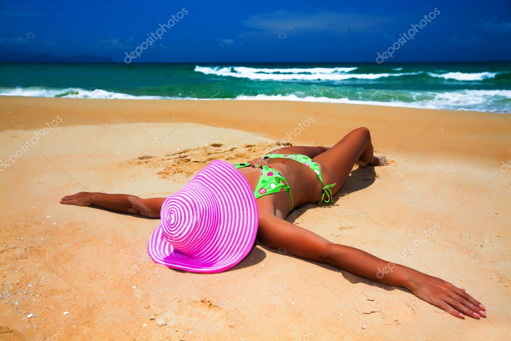 Woman in pink hat lies on the beach  Foto de Stock   #2574911