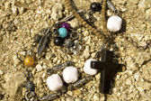 Necklace, beads and cross on the sand — Stock Photo