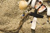 Kolye, boncuk ve kum üzerinde çapraz — Stok fotoğraf