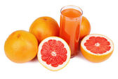 Glass of juice and grapefruits — Stock Photo