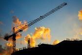 Hoisting crane silhouette on sunset sky — Stock Photo