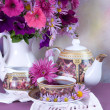 Cup of tea and a bouquet of flowers in a white jug — ストック写真