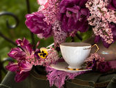A cup of coffee and a bouquet of lilacs — Stock Photo