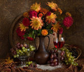 Still life with autumn flowers, grapes and wine — Stock Photo
