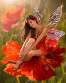Brunette girl elf with is sitting on a flower poppy — Stock Photo