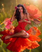 Brunette with wings sitting in a flower — Stock Photo
