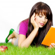 Woman lays on green grass with book — Stock Photo #1600962