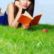 Woman lays on green grass with book — Stock Photo #1601224