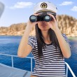 Woman looking through binoculars — Stock Photo