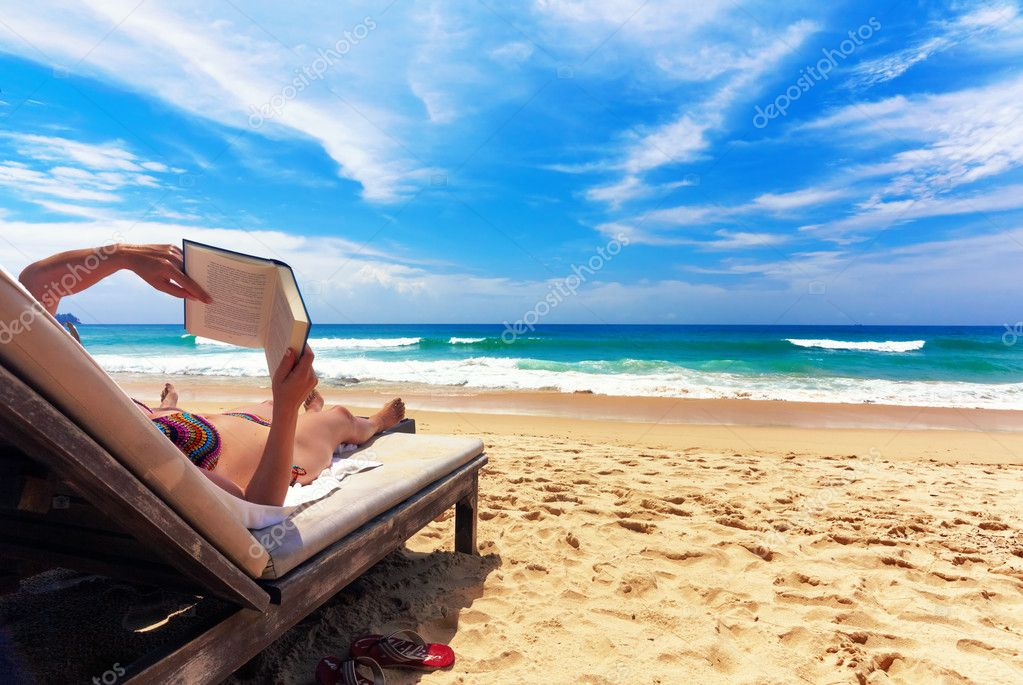 Gigrl reading book ana relaxing on the beach — Stock Photo #1583655