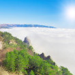 Стоковое фото: High mountain over white clouds