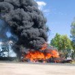 Truck in fire with black smoke on the ro - Foto Stock