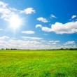 Green hill under blue cloudy sky whit su — Stock Photo