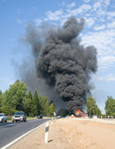Truck in fire with black smoke on the ro — Stock Photo