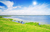 Lake, green grass and blue sky — Stock Photo
