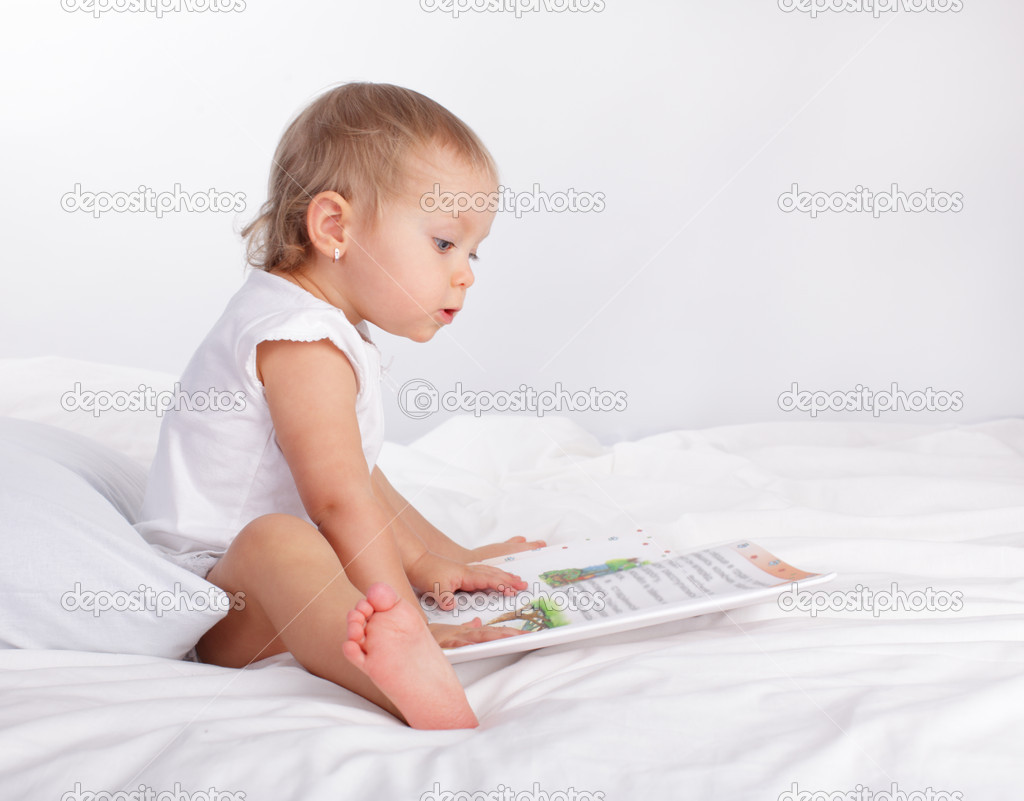 Baby reading book on t...