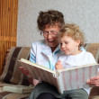 Grandmother reading book to the granddaughter - Stock Photo