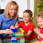 Happy mum with children plays cubes — Stock Photo