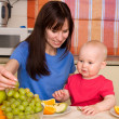 Beautiful happy mum with son eat fruit — Stock Photo #1843397