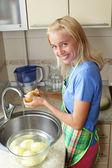 Beautiful woman cleans a potato — Stock Photo
