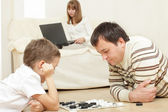 Father with the son playing draughts — Stock Photo