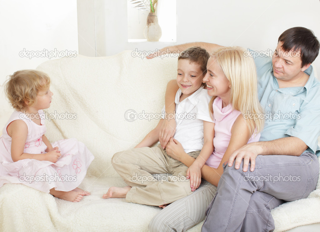 Happy family with two children on sofa — Stock Photo #2405165